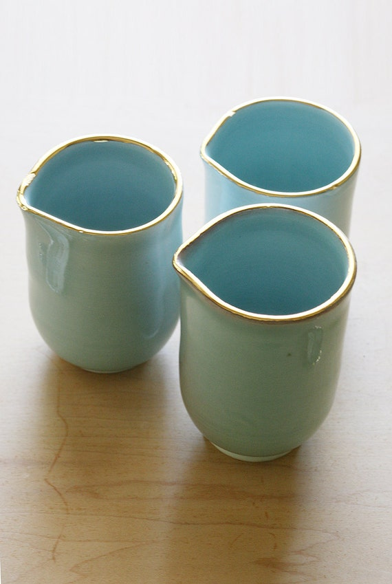Set of 3 Wheel Thrown Porcelain handle-less pitchers with blue delicate glaze and gold rims
