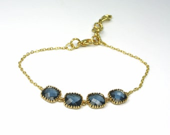 navy blue bracelet with square framed and faceted  briolettes in gold bezel settings geometric and delicate