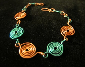 Wire bracelet with peach and light blue spirals