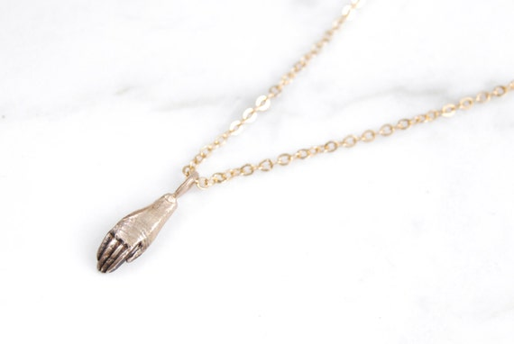 Tiny golden hand necklace
