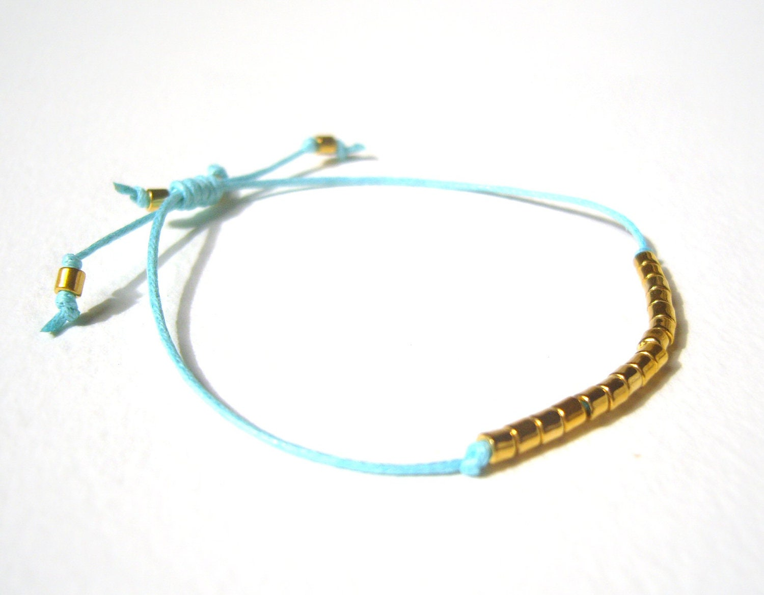 what does the string bracelet beaded string bracelet bright blue cord bracelet gold bead 7072