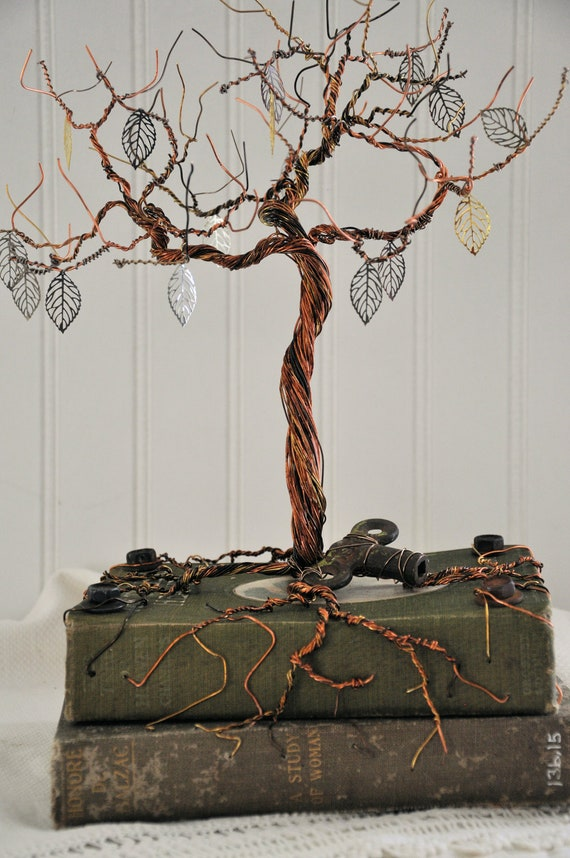 Tree assemblage with various wires on two  vintage books with found objects.