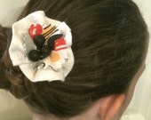 Floral pin and hair clip crafted from vintage linens and antique buttons in cream, red, yellow and black