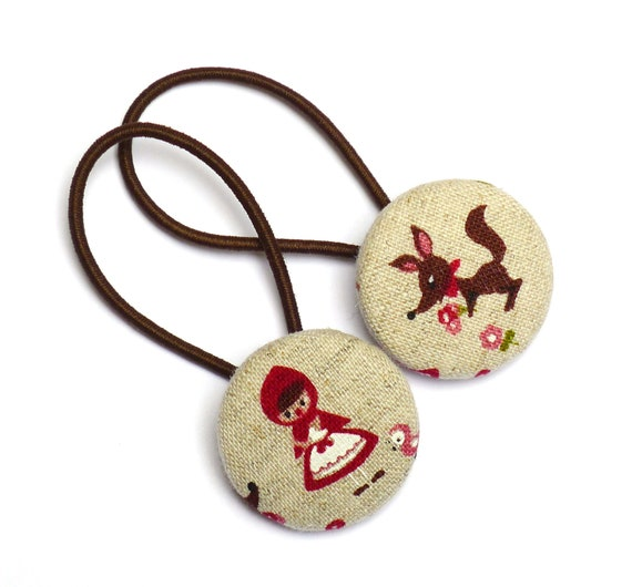 A pair of hair elastics, ponytail holders, RED RIDING HOOD