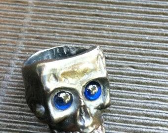 Sterling Silver Anthropomorphic skeletal head ring w/ Blue Sapphire peepers
