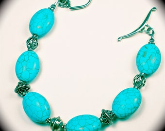 Lovely turquoise colored magnesite stones and sterling silver beaded bracelet.