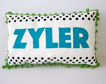 Baby pillow with black polka dots and personalized with bright turquoise name.