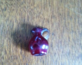 Tiny Toy Pitcher of Cranberry or Ruby Glass with clear Handle.