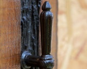 Clothes hanger made of arc-décor door handle on old wood