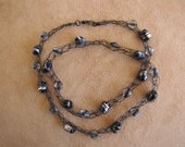 Black wire with black/silver barrel beads and clear bi-cone beads. 24 inches in length.
