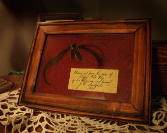 Lock of Edgar Allan Poe's hair, preserved in wooden frame