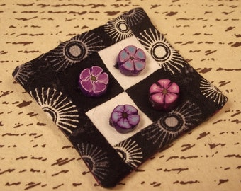 Black and white quilted fabric pin brooch with purple and blue flowers.