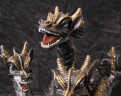 Five-headed, smoke-emitting dragon. Black with gold scales and gold talons.  Each head has different colored metallic eyes.