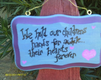 We hold our childrens hands sign