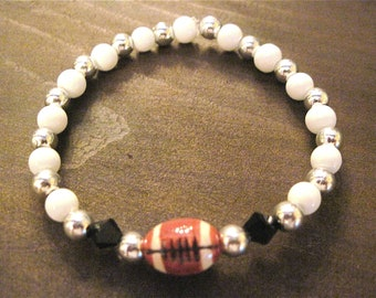 Football Bracelet ceramic brown football 11 mm surounded by two black crystal accent, white and silver metal beads. 2012036
