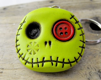 Lime green round skull with a red button in his eye. Brooch, keychain, pendant or magnet (you choose)