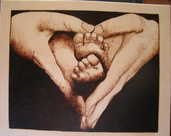 Precious baby feet cradled in hands like a heart hand burned pyrography