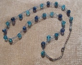 Light blue knit wire necklace with blue bicone and foil lined beads. 22 inches in length.