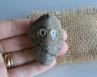 Pet Rock wearing glasses with funny natural smile with burlap pillow bed