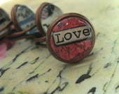 Inspirational expression of Love beneath magnifying glass dome, bezel set in antiqued copper tone base