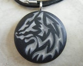 Tribal Wolf hand carved on a polymer clay black color background. Pendant comes with a FREE 3mm Necklace