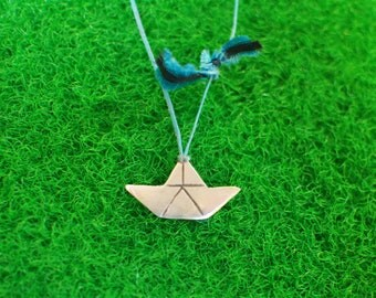 Sterling silver boat-shaped pendant on waxed string