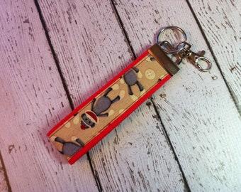 Sock Monkey print key fob wristlet on red cotton webbing with swivel lobster clasp