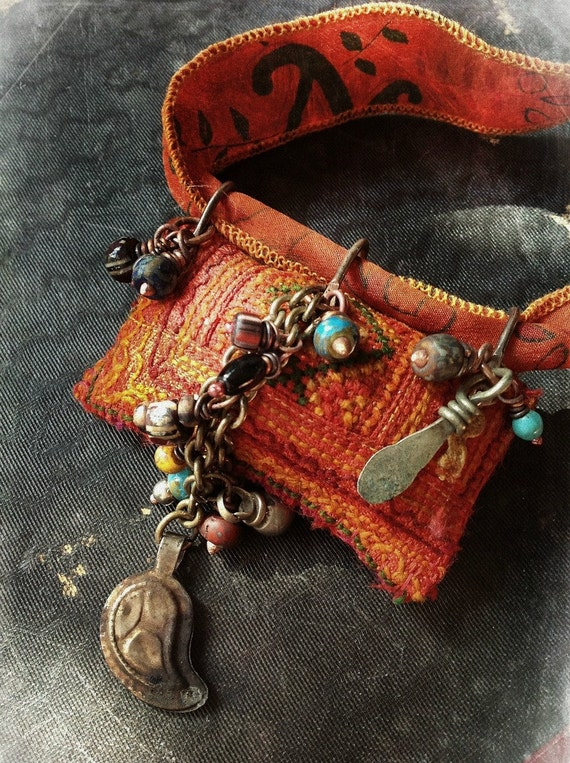 Gypsy amulet necklace with richly embroidered textiles and bead cluster in deep orange
