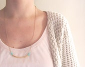 Geometric necklace. Minimal jewelry. Golden arc tube with aquamarine czech beads