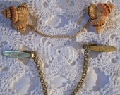 2 Vintage Sweater Clips-1 is a Gold toned Metal that looks like a tie clip-the Other is a Trio of Sea Shells & pearls-pretty