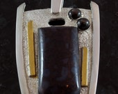 Dinosour bone with black star sapphire, silver and gold pendant