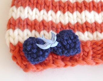 Girl's knitted striped beanie hat in coral and ivory with blue swallow bow