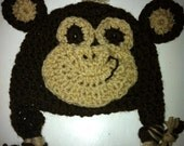 Monkey hat in crochet, made in dark brown and beige with ear flaps and braids
