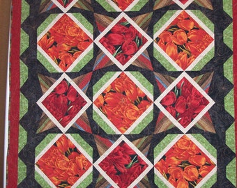 Quilted wall hanging or lap quilt. Machine pieced and quilted in beautiful red and orange tulips