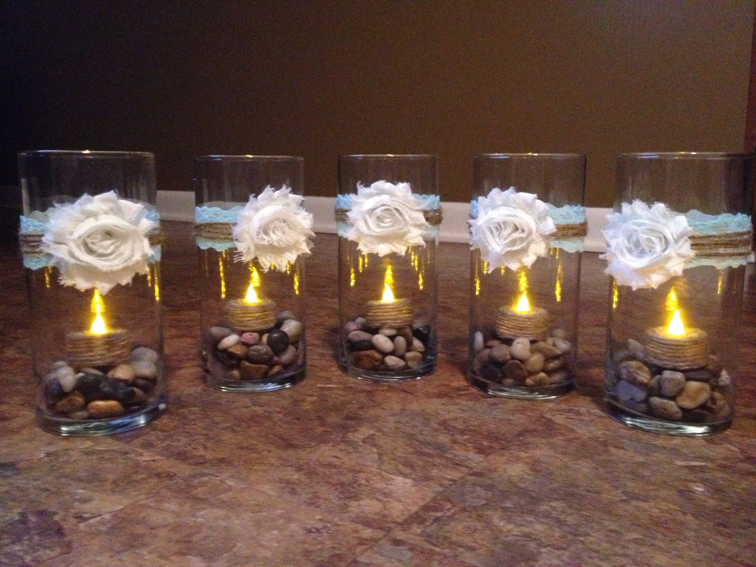 Vase centerpieces with rocks and led tea lights by leahluxe