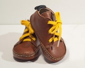 Baby shoes in toffee brown colour, 100% leather inside and outside. Yellow or beige cotton laces.Size EU17 UK2 US 2.5