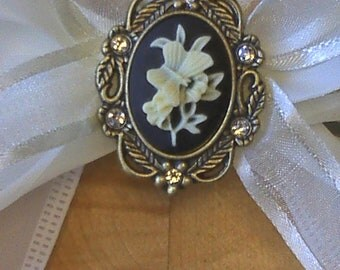 Cream and Gold Ribbon with a Black and Cream Flower Metal Broach Center Piece