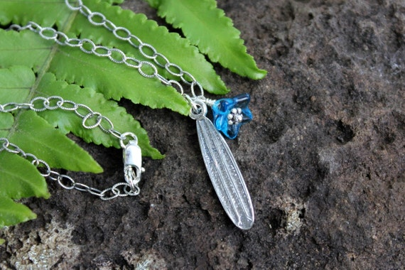 Surfer girl necklace - sterling silver surf board and blue glass flower on an oxidized textured sterling chain