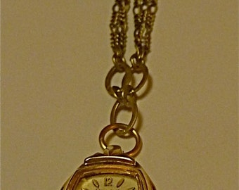 Repurposed vintage mixed metal necklace with a Bulova women's watch pendant and glass bead charm