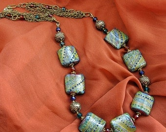 Glass lampwork necklace with square beads and bronze color finding. Green, olive and deep blue color.