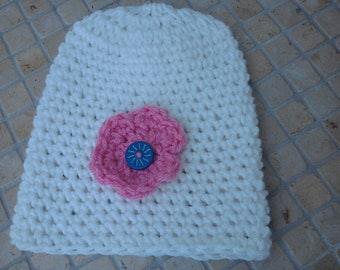 white childs hat with pink flower and blue button