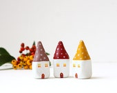 Little autumn village with three clay houses with polka dots on the roof