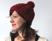 Crimson red knit pompom winter hat with cables