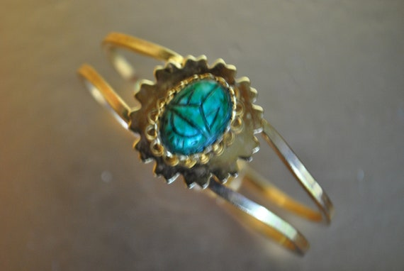 Egyptian revival.Vintage 80s goldtone metal hinged cuff bracelet with green scarab.