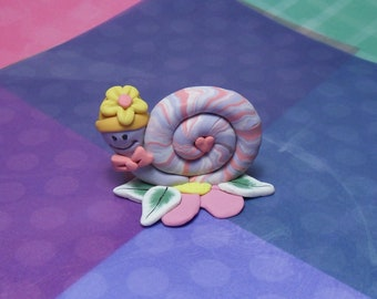 Handmade polymer clay snail with Hat with flower sitting on flower with leaves wearing a bowtie
