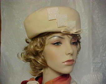 SALE.   White wool pill box hat with ribbon tabs in front and a bow- fits 22 1/2 inches