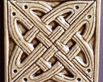 Decorative, relief carved ceramic Celtic knot tile