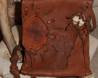 Light Rays- This Wisdom Bag is made out of Brown Leather and features a Deer antler button and Carved Symbols