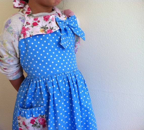 Girl apron, white polka dots on a blue fabric.