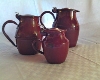 Three Antique  enamelware pitchers with covers